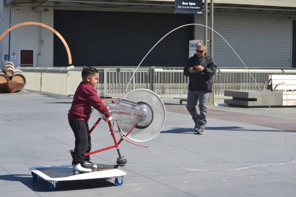 Outside San FranciscoÍs Exploratorium on Pier 15, kids work a bike-like wheel called a Bicycle Rope Squirter. The image ...