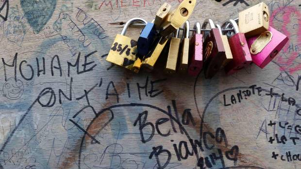 A panel with love locks and personal messages is seen of the Pont de l'Archeveche bridge.