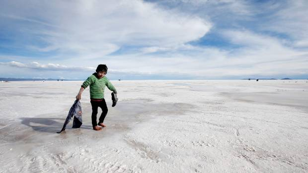 A boy plays in the salt at the Salar de Uyuni or Uyuni Salt Flat in Uyuni, Bolivia.