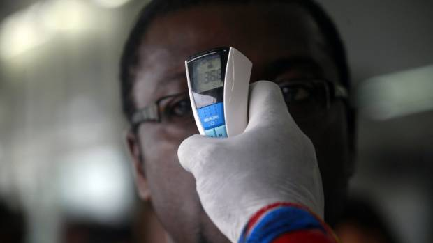 ARE YOU SAFE? A health worker takes a passenger's temperature with an infrared digital laser thermometer at the Felix ...