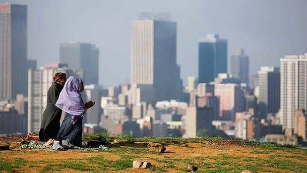 Follow the rainbow: Worshippers in prayer on a hill overlooking Johannesburg in 2013 following news of Mandela's death.