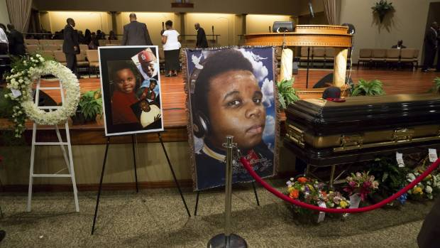 MOURNED: Photos surround the casket of Michael Brown.