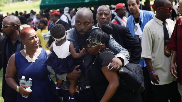 IN MOURNING: Michael Brown Sr receives a hug as he leaves the burial service for his son Michael Brown.
