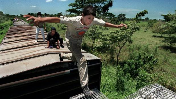 Denis Contreras watches 13-yr-old Jose Padilla Guerra make his very first leap between cars of a moving freight train in ...