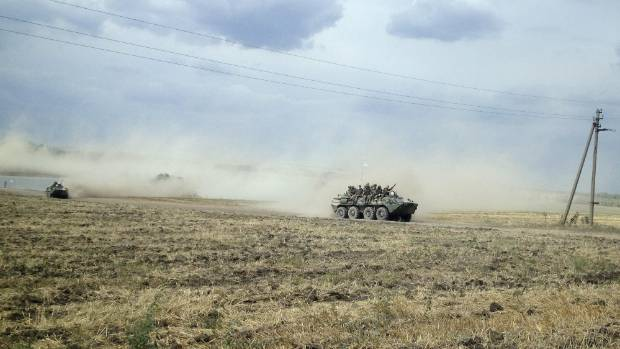 Armoured vehicles, suspected of carrying Russian troops drive across the Ukrainian countryside near the village of ...