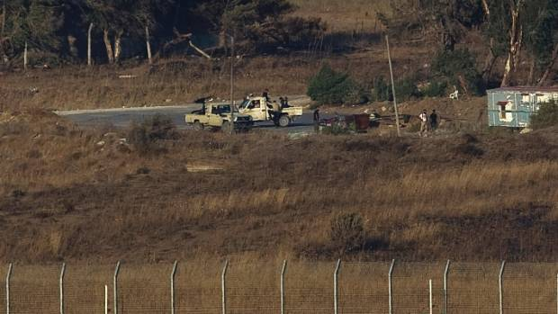 Militants are seen on the Syrian side near the Quneitra border crossing between the Israeli-controlled Golan Heights and ...