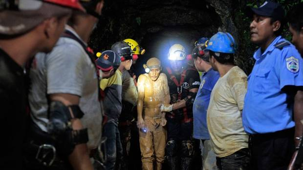 OUT: Miners and rescue workers hold a miner covered in mud after he was rescued from a gold mine blocked by a landslide ...