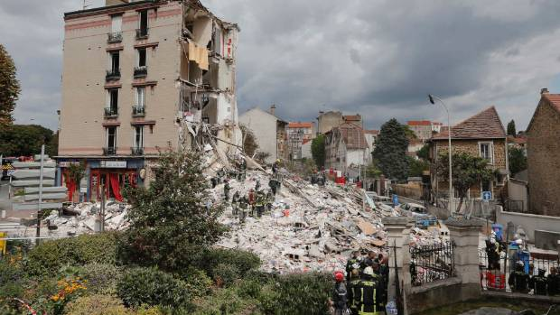 French firefighters search the rubble of a collapsed building, where at least eight people were killed.