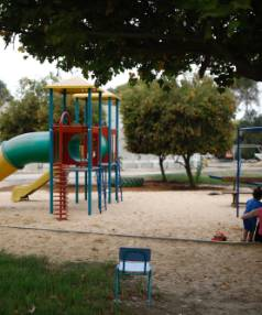 An Israeli woman and a child sit at a playground near a kindergarten surrounded by concrete blast walls (rear), erected ...