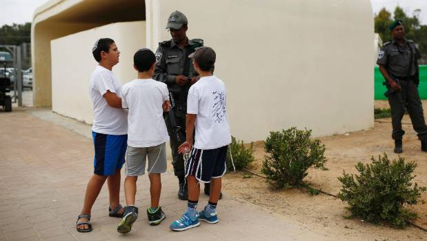 Israeli children speak with a police officer as they stand next to a bomb shelter on the first day of the school year in ...