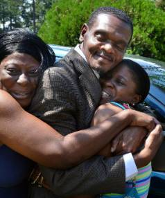Tracey O'Neal, right, and her sister Michelle Wallace hug their cousin Henry McCollum as he arrives home.