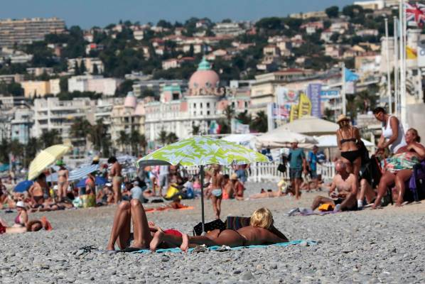 People enjoy a sunny and warm day on a beach in Nice, France.