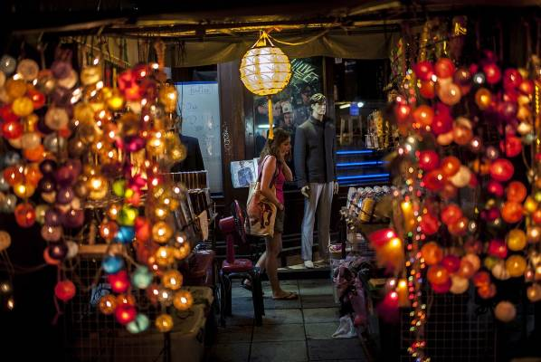 A tourist is seen through a lamp shop in Khao San road in Bangkok, Thailand.