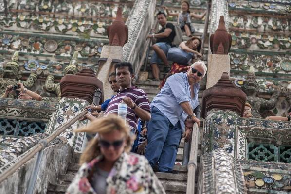 Tourists go down from the top of Wat Arun temple in Bangkok, Thailand.