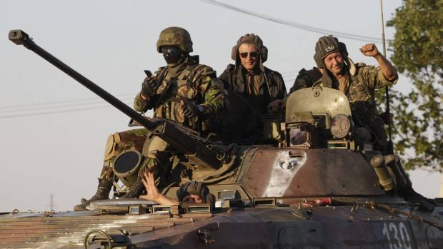 Ukrainian servicemen ride on an armoured vehicle in Mariupol following the ceasefire.