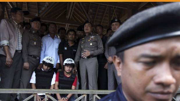 Thai national police chief Police General Somyot Poompanmoung (centre) stands next to two detained workers from Myanmar, ...