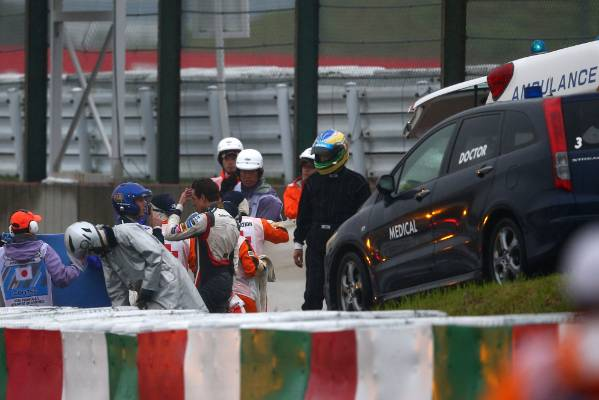 A distressed Adrian Sutil of Sauber speaks to a doctor while Jules Bianchi receives urgent medical attention following ...