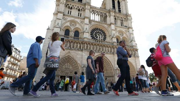 People stand in line outside Notre Dame Cathedral in Paris. France is the world's number one destination.