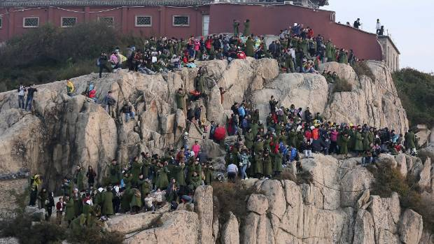 Tourists crowd on the mountain edge as they watch a sunrise on a peak of Mount Tai, on the first day of the seven-day ...