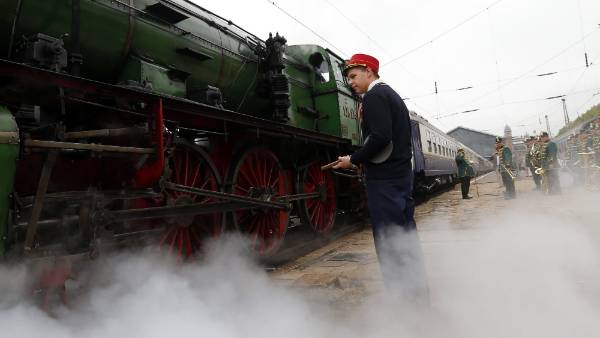 A conductor stands in front of a historic steam locomotive as it pulls the luxury Tehran-bound train into Nyugati ...