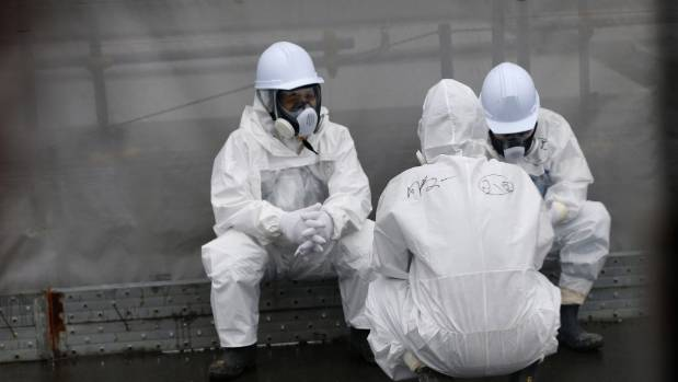 Workers wearing radiation protective gear rest on a road at TEPCO's tsunami-crippled Fukushima Daiichi nuclear power ...