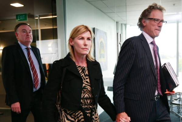 Cera chief executive Roger Sutton walks into a press conference to announce his resignation, holding wife Jo Malcolm's ...