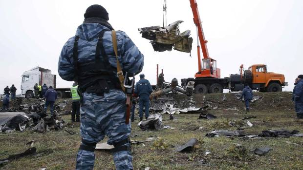 WRECKAGE RECOVERY: A pro-Russian separatist watches as a crane carries wreckage of the downed Malaysia Airlines flight ...