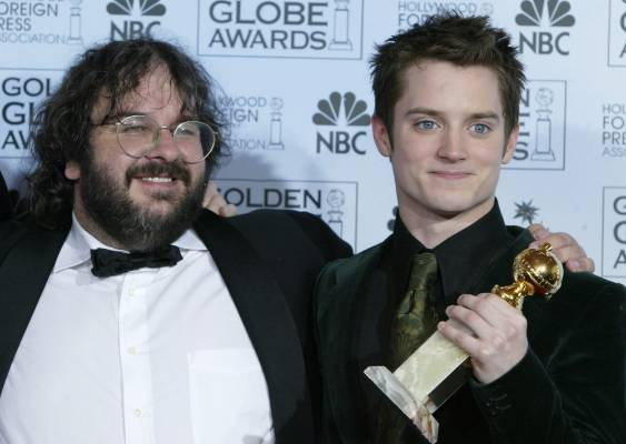 Peter Jackson (L) and actor Elijah Wood pose with their Golden Globe Award after The Lord of the Rings: The Return of ...