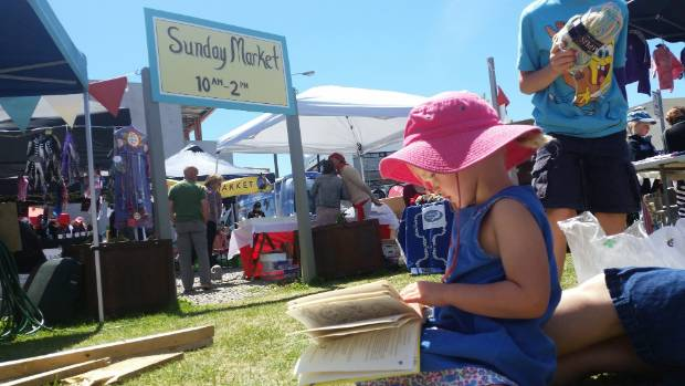 ENGROSSED: Cara MacPherson, 4, reads a book at the Sumner Sunday Market.