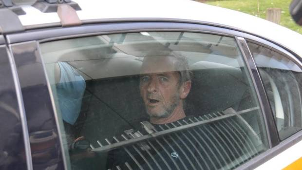 BACK IN CUFFS: AC/DC drummer Phil Rudd is taken away in a police car after an incident in Gate Pa.