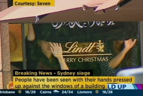 Hostages can be seen inside the cafe holding an Islamic flag up against the window.