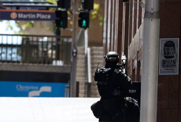 A police officer pointing his weapon towards the siege.