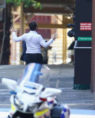 After almost six hours being held inside a central Sydney cafe, a hostage ran outside as armed police gestured to him. ...
