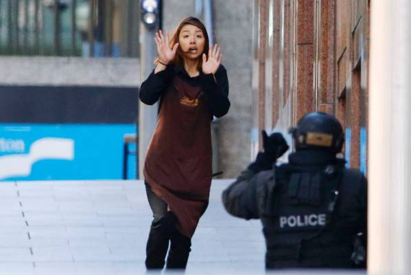 A woman runs from the cafe several hours after the hostage drama began in Sydney's CBD.