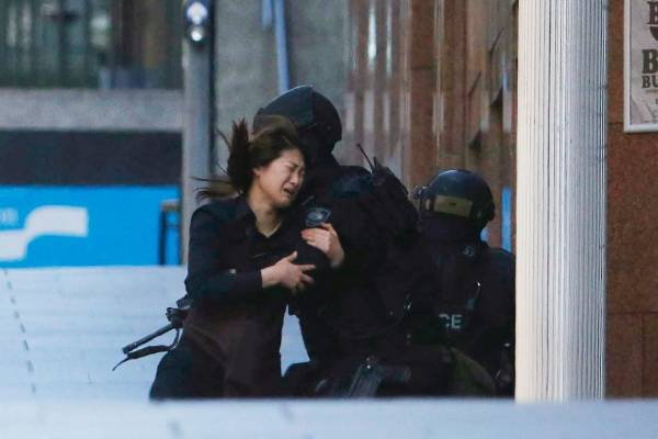 A woman collapses into the arms of a policeman as she runs to safety from the cafe.