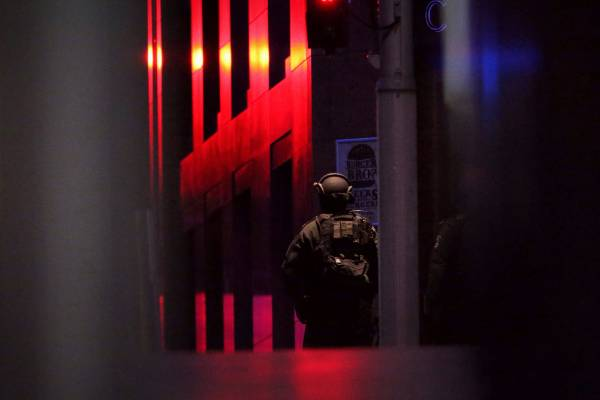 NSW Tactical Operations Unit police officers keep watch outside the Lindt Chocolate Cafe before the siege ended.