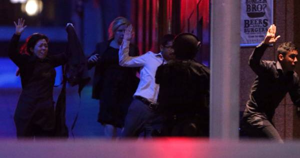 Hostages flee from the Lindt Chocolat Cafe in Martin Place in Sydney.