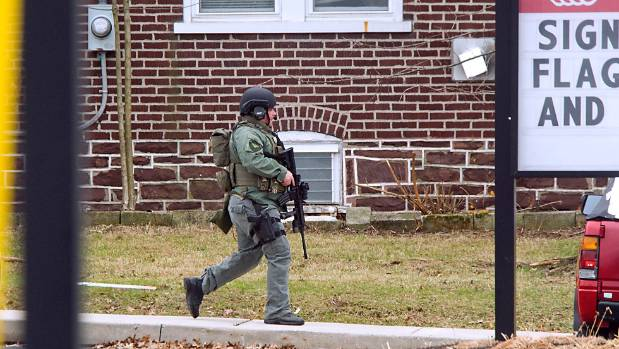 A special weapons officer heads toward the command center in Souderton, Pennsylvania.