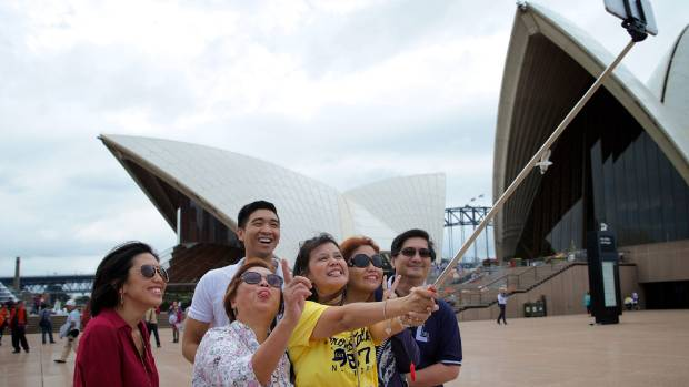 Tourists use a selfie stick to photograph themselves at the Sydney Opera House.