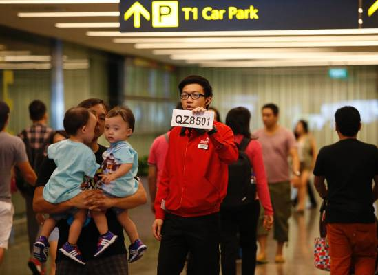 A Changi Airport staff holds up a sign to direct possible next-of-kins of passengers of AirAsia flight QZ 8501 from ...