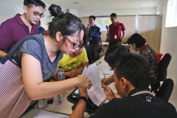 Relatives of the passengers on board AirAsia flight QZ8501 check the plane's manifest at a crisis centre set up by local ...