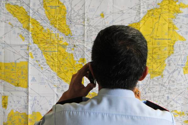 An airport official checks a map of Indonesia at the crisis centre.