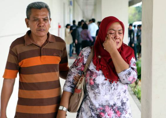 A relative of the passengers of AirAsia flight QZ8501 weeps as she waits for the latest news on the missing jetliner.