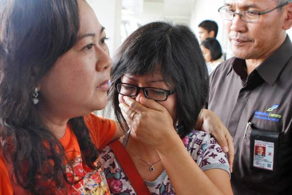 A relative of Air Asia flight QZ8501 passengers weep as she waits for the latest news on the missing jetliner.