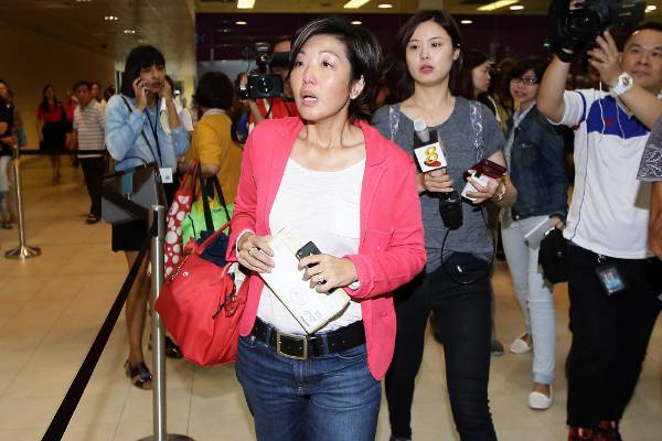 A woman arrives at a holding area for friends and relatives of passengers on AirAsia flight QZ8501 at Changi Airport in ...