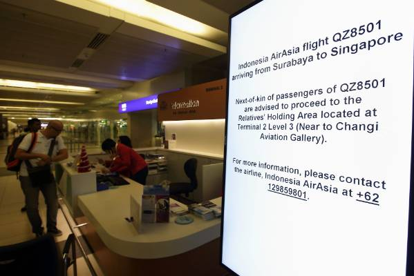 A sign provides information for friends and relatives of passengers on AirAsia flight QZ8501 at Changi Airport in Singapore.