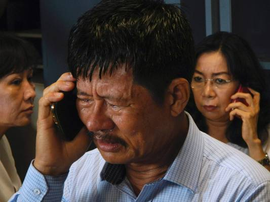 Family members of passengers on board AirAsia flight QZ 8501 talk on their phones while waiting for information inside a ...