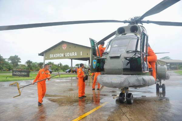 A search and rescue squad from the Indonesian Airforce prepare to depart on a Puma helicopter to take part in the search ...