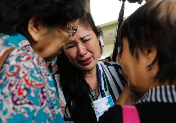 Relatives of passengers onboard AirAsia flight QZ8501 cry in a waiting area at Juanda International Airport in Surabaya.