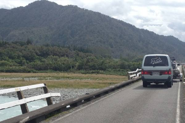 A car smashed through bridge railings into the Wanganui River on the West Coast.